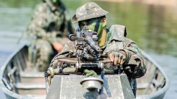 Militar de uniforme camuflado aponta rifle