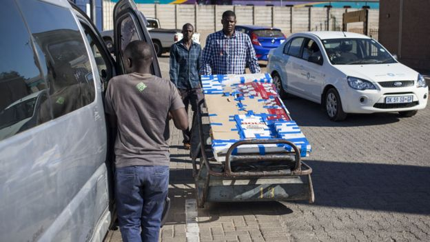 Man loading goods into a minibus