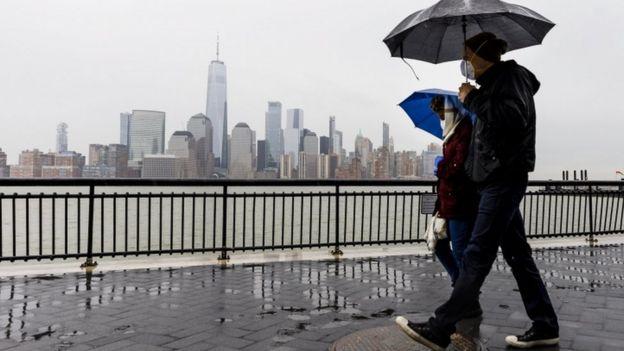 Duas pessoas usando máscaras caminham sob a chuva segurando guarda-chuvas com a cidade de nova york ao fundo, do outro lado do rio