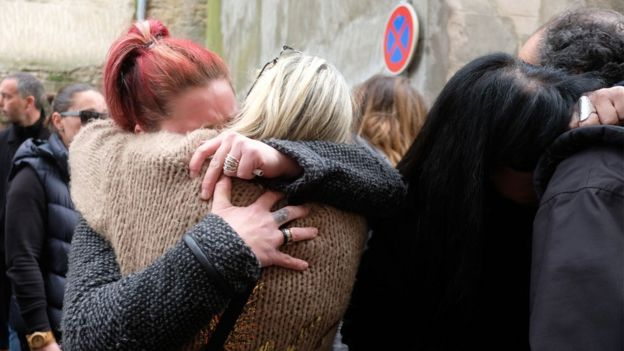 People console each other outside the Saint Etienne Church in Trebes in southwest France, after a service of remembrance to victims