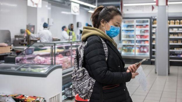 mulher no mercado com mascara