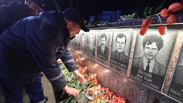 Ukrayna'nın kuzeyindeki bir Çernobil anıtına itfaiyeciler çiçek bırakıyor (2018)