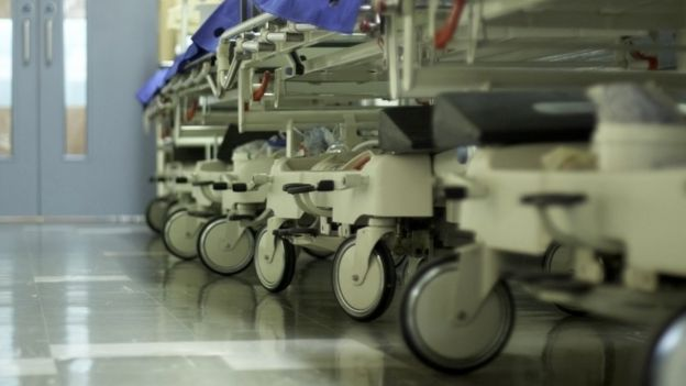 A hospital corridor with beds lined up in a row