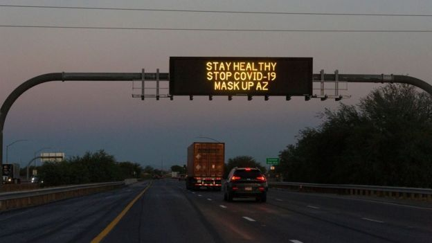 A freeway sign reads 'stay healthy, stop Covid-19, mask up AZ'