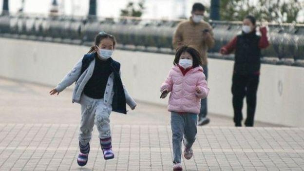 Dos niñas con mascarillas corren mientras sus padres las observan en el fondo
