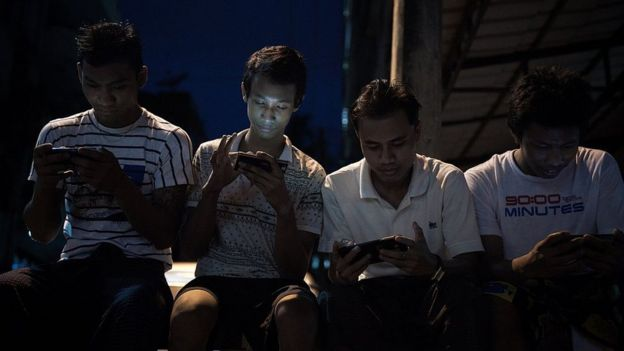Personas consultan sus celulares en Camboya.