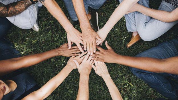 Brazos de varias personas con colores de piel diferentes.