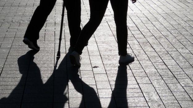 Pareja caminando y sus sombras.