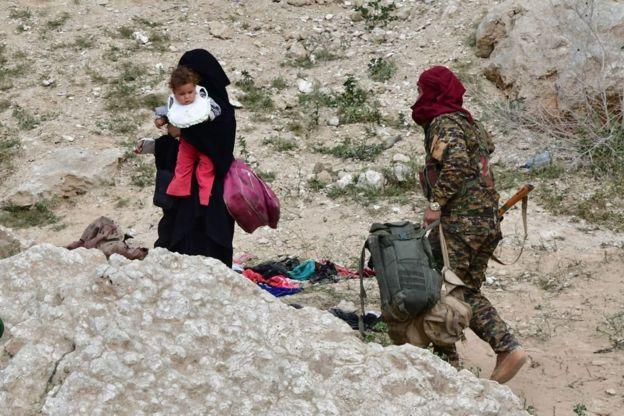 أحد أفراد قوات سوريا الديمقراطية يساعد إحدى عائلات مسلحي التنظيم على الخروج من بلدة باغوز في محافظة دير الزور شرقي سوريا. 14 مارس/آذار 2019