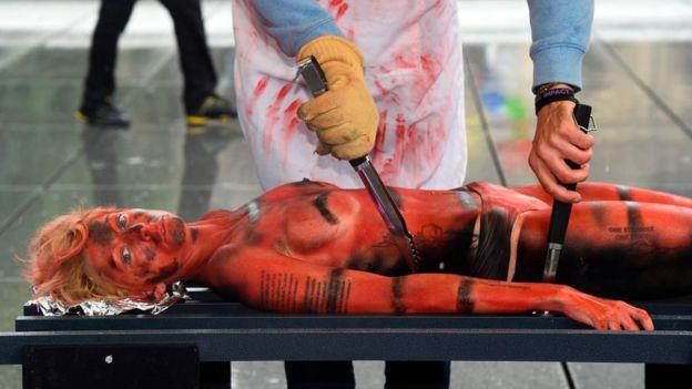 Mujer disfrazada de carne cruda en protesta.