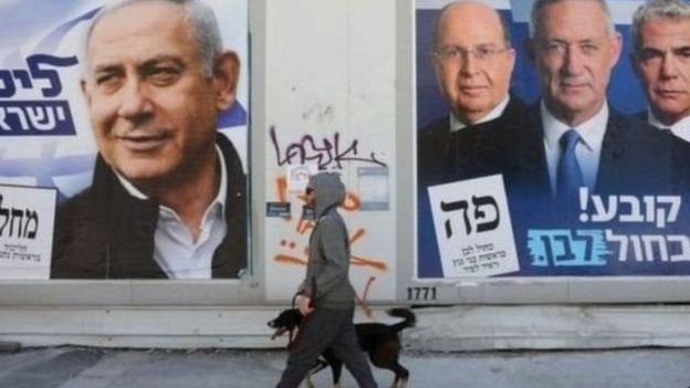 चुनाव के पोस्टर के सामने गुजरता एक व्यक्ति