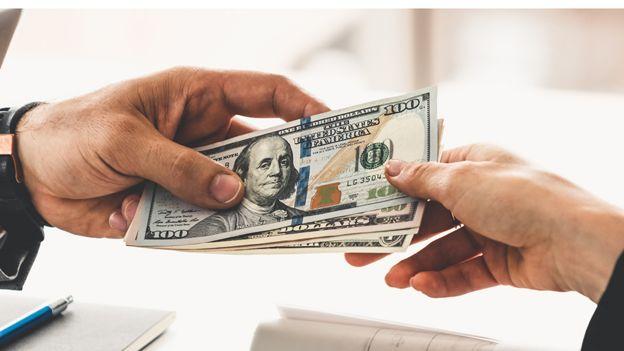 Una persona le entrega dólares a otra