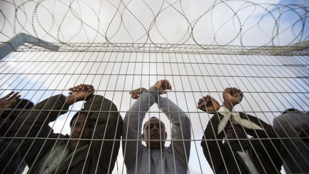 African asylum seekers, who entered Israel illegally via Egypt, lean at the fence of the Holot detention centre in Israel's southern Negev Desert, on February 17, 2014 as they join other migrants who came to protest outside the detention facility.