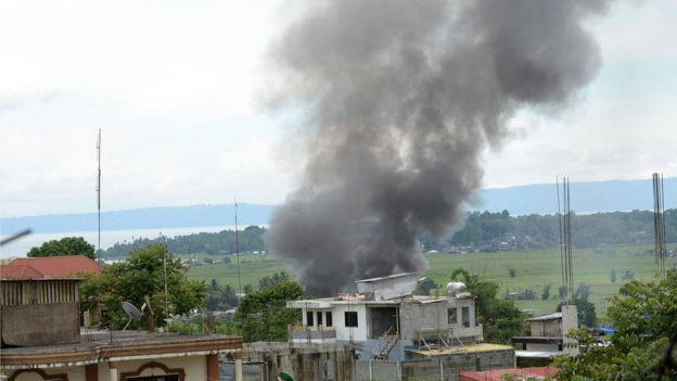 Black smoke billows from burning houses as fighting between Philippine soldiers and the IS-affiliated Maute group rages near the provincial capitol in Marawi, on the southern island of Mindanao on 25 May 2017