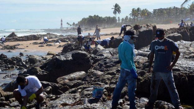 Com Farol de Itapuã ao fundo, voluntários trabalham na limpeza do óleo em Salvador