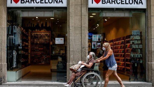 женщина везет в коляске пожилую женщину в Барселоне