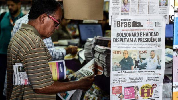 """Foto mostra homem lendo jornal ao lado de outro exemplar que diz: """"Bolsonaro e Haddad disputam a presidência"""""""