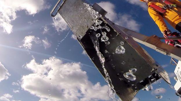 O gravador sendo retirado da água por uma pessoa