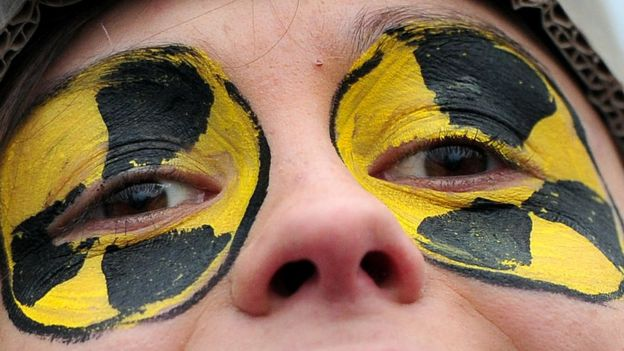 A nuclear protestor with the radiation symbol painted around her eyes