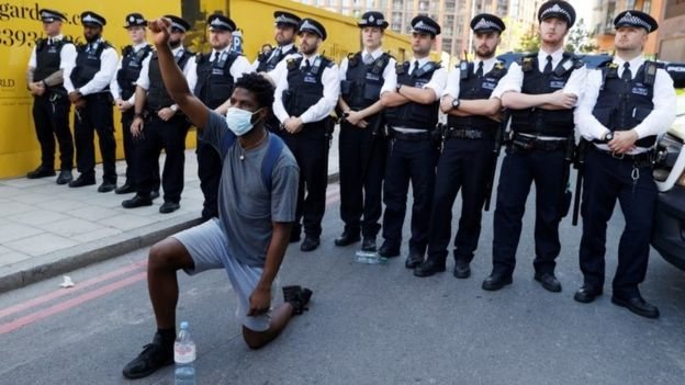 Police stand behind a protester