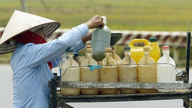 Một phụ nữ bán xăng bên lề đường