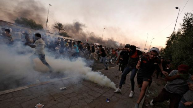 Demonstrators run away from tear gas in Baghdad