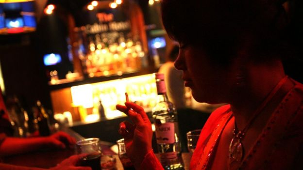 Local woman drinking and smoking in a bar