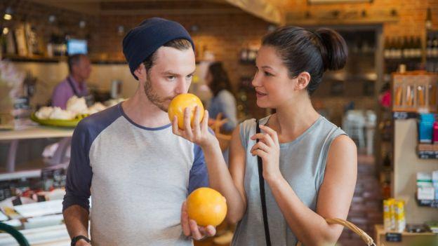 Una pareja oliendo pomelos en un mercado