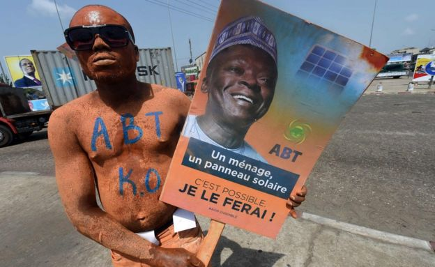 A picture taken on March 4, 2016 shows a supporter with the party colours carrying a poster of presidential aspirant and former head of the West African Development Bank Abdoulaye Bio Tchane during a rally in Cotonou