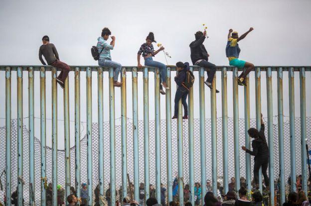 Pessoas sobre a cerca de separa os Estados Unidos do México