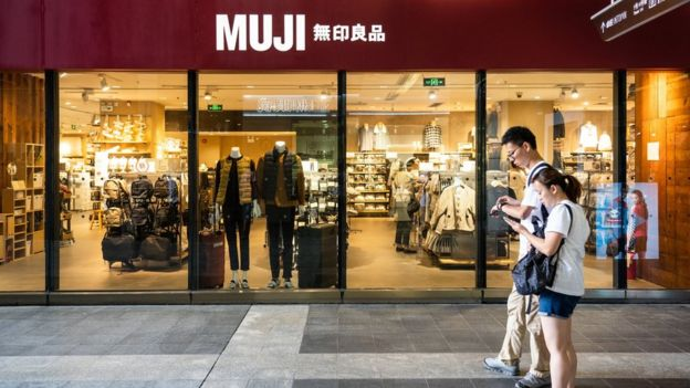 Pedestrians walk past a Japanese household and consumer goods retailer, Muji store in Shenzhen