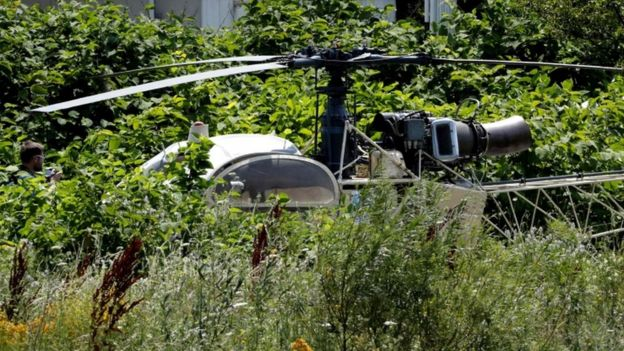The helicopter sits in a field surrounded by thick foliage