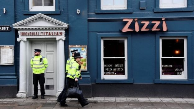A police officer stands outside a restaurant which was closed after former Russian inteligence officer Sergei Skripal, and a woman were found unconscious on a bench nearby