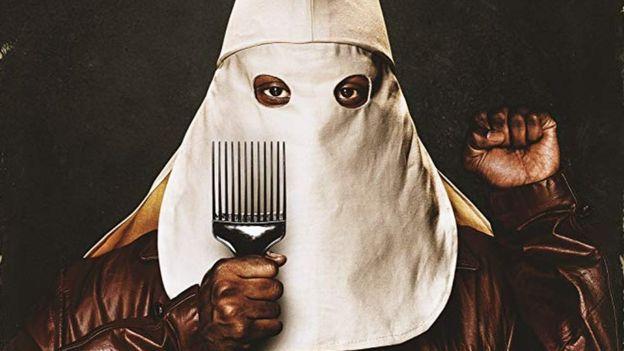 Un zoom del afiche de la película que muestra al protagonista llevando una capucha del KKK junto a una peineta para su afro y alzando la mano izquierda como solía hacerlo el partido de las Panteras Negras.
