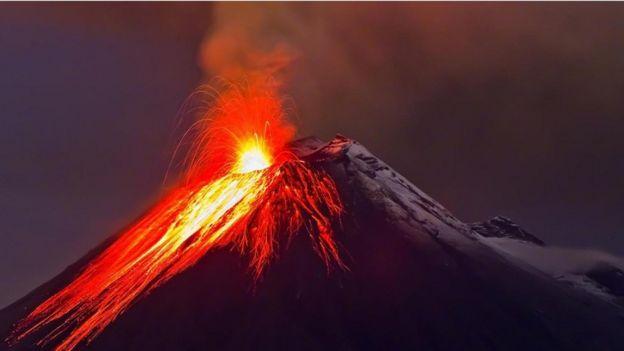 Una foto nocturna de un volcán haciendo erupción