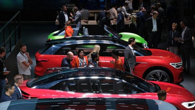 Visitors look at Volkswagen electric cars during the press days at the 2019 IAA Frankfurt Auto Show
