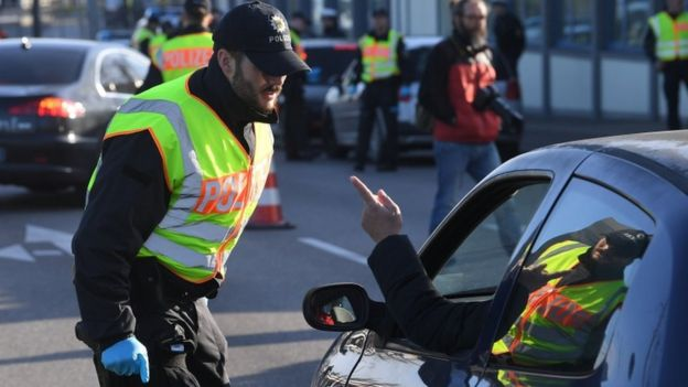 A German police officer controls a motorist at the French-German border between Kehl and Strasbourg