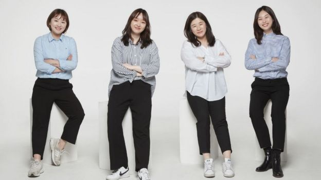 The four female members of Ease & More team pose on stools in promotional image