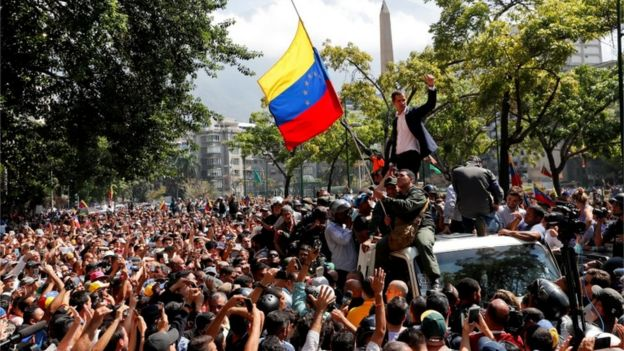 Juan Guaidó standing on top of a car amid street demonstrations in Caracas, 30 April 2019