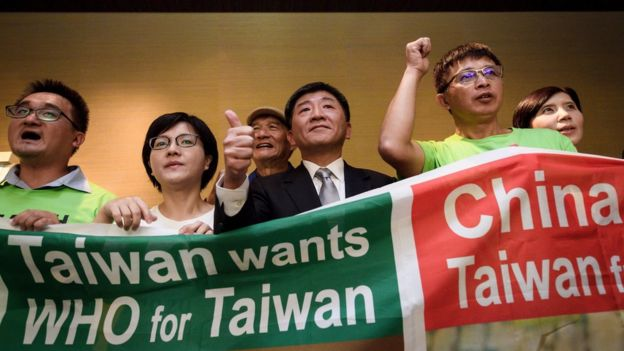 Taiwan's health Minister Chen Shih-chung (C) gives a thumb up as he poses with demonstrators after a press conference on the sideline of the World Health Organization annual Assembly on May 21, 2018 in Geneva.
