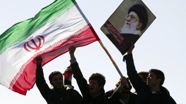 Iranians waving flag and picture of Ayatollah Ali Khamenei