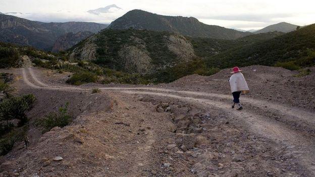 Un mujer camina por una carretera de tierra en Hidalgo, México.