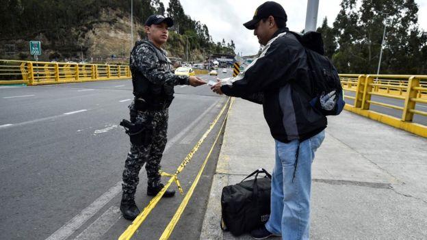 Un migrante venezolano muestra sus papeles en la frontera con Ecuador