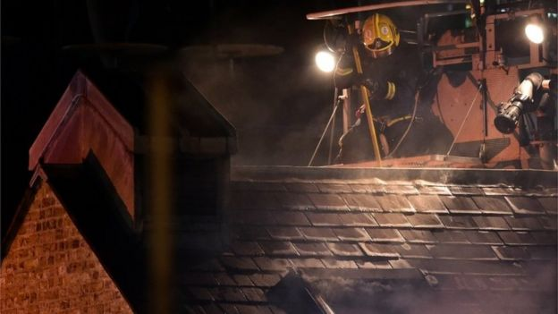 Firefighter on roof of burning Camden Lock building