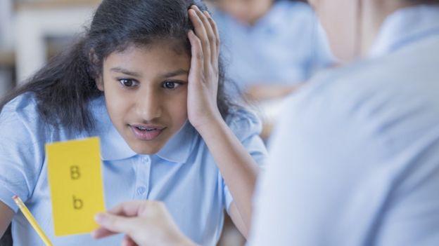 """Una niña intenta leer con dificultad una tarjeta con las letras """"b"""" en minúscula y mayúscula."""