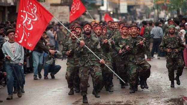 Integrantes do Hezbolá segurando armas e bandeiras