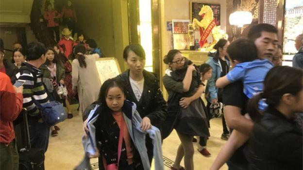 Tourists leave a hotel in in Ruo'ergai, Sichuan