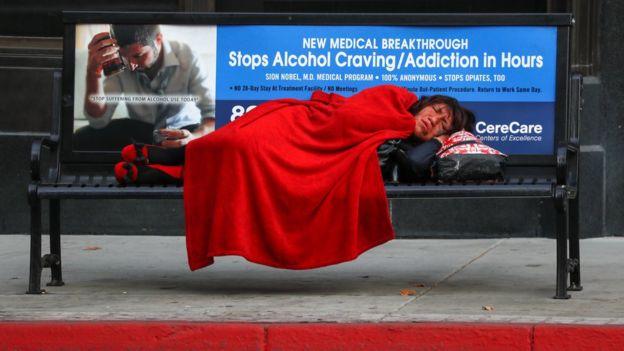 Moradora de rua dormindo em banco em uma rua de Los Ângeles
