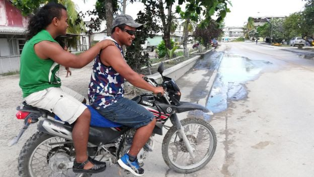 Two men riding their motorbike on the quiet streets of Aiwo on the Pacific island of Nauru on 1 September 2018