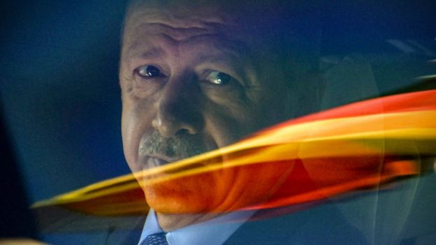 Turkish President Recep Tayyip Erdogan sits in a car behind a reflection of the German flag as he departs after his arrival from the Berlin Tegel Airport for an official visit in Berlin, Germany, 27 September 2018.